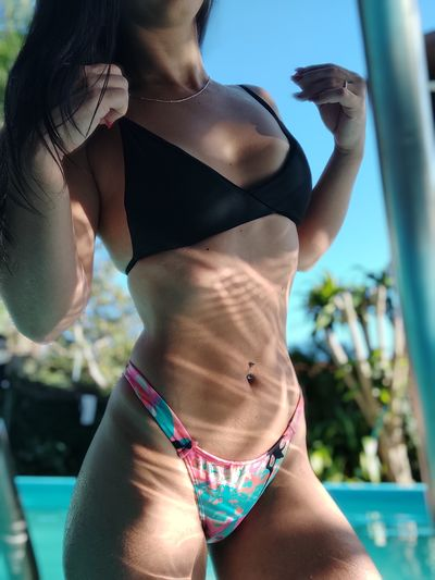 Midsection of woman in bikini standing by swimming pool