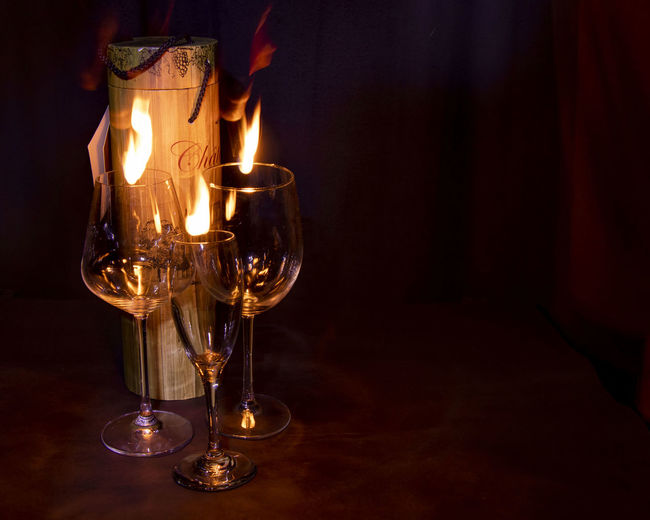 Wineglasses by fire on table in darkroom