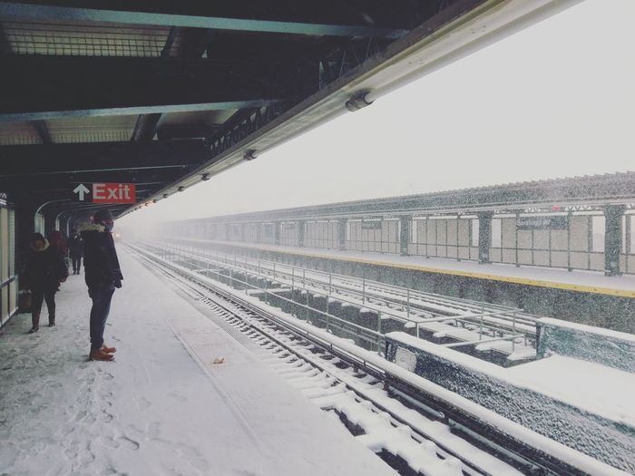 Rear view of woman at railroad station during winter