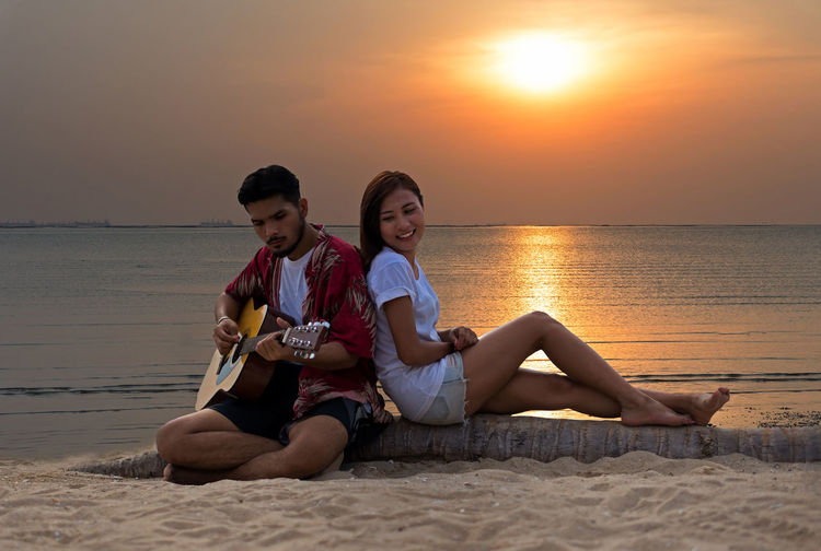 Friends sitting on shore at beach against sky during sunset
