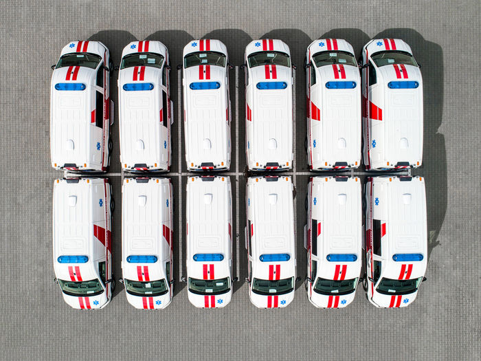 Directly Above Shot Of Vans Parked On Road During Sunny Day