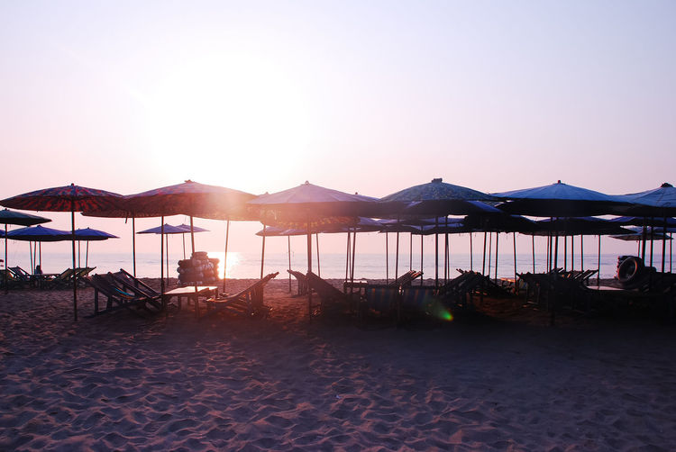 Parasols And Chairs At Beach Against Clear Sky During Sunset