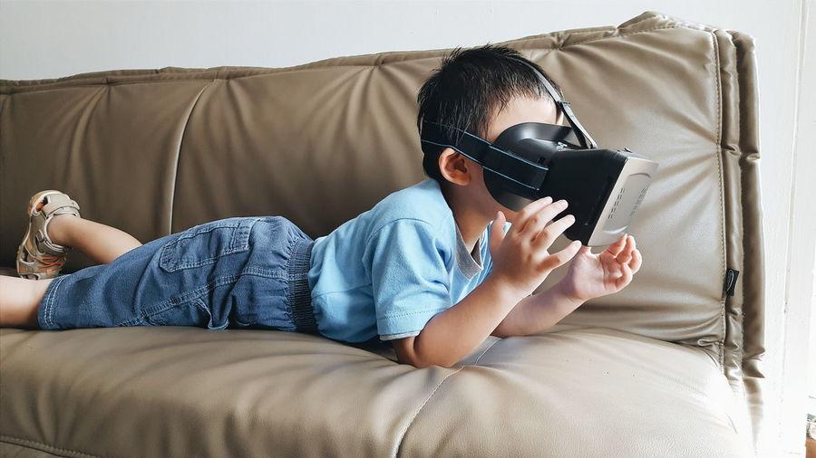 Boy using virtual reality simulator on sofa at home