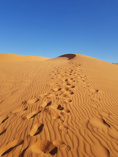 Sand Dunes In Desert Against Clear Blue Sky