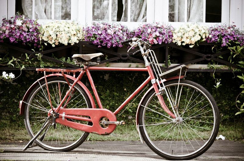 Bicycle parked by window boxes outside houses