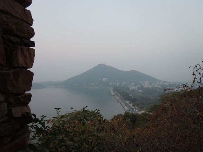 Scenic view of fateh sagar lake by mountain against sky seen from moti magri