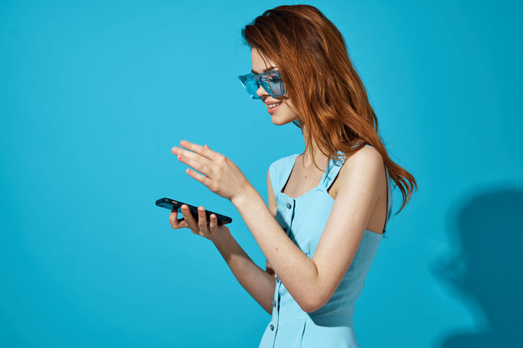 Young woman using phone while standing against blue sky