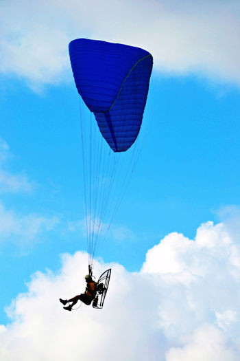 Person motor paragliding against sky