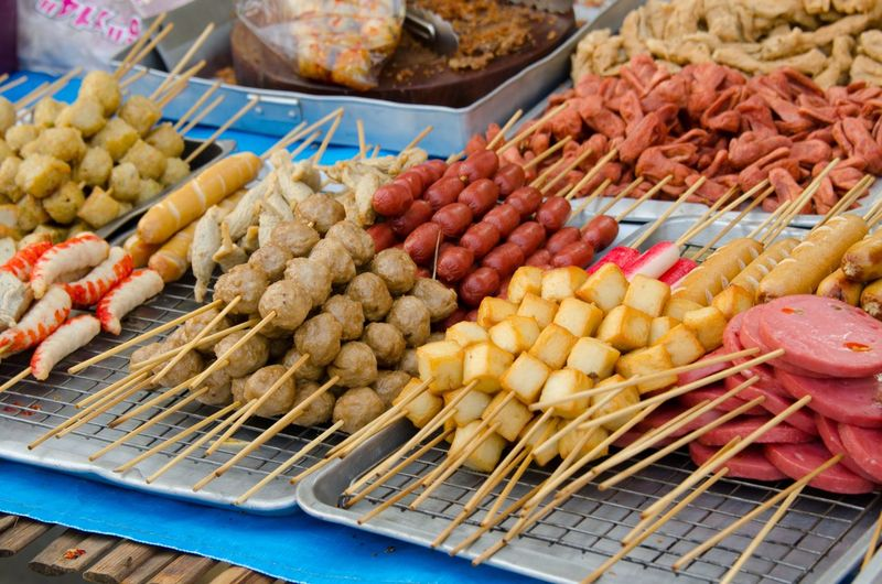 High Angle View Of Fresh Skewered Food In Tray At Market Stall