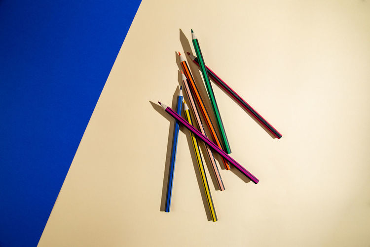 High angle view of multi colored pencils on table against blue background