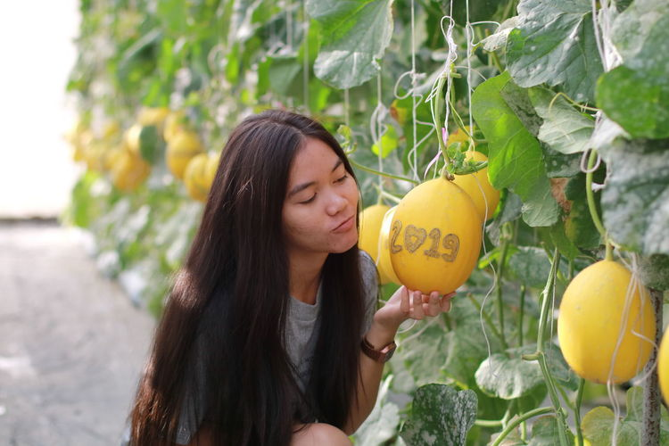 Smiling young woman holding fruit with numbers