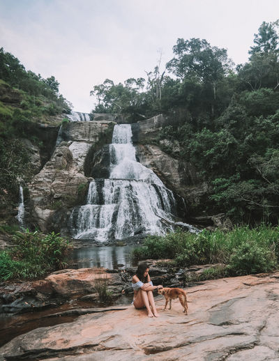 Woman with dog on rock against diyaluma falls