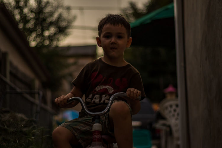 This is a shot of my four year old on his favorite tricycle riding up and down the sidewalk. Bokeh Casual Clothing Child Day Depth Of Field EyeEm Gallery Focus Focus On Foreground Fun Holding Kid Kid Photography Lifestyles Person Son This Week On Eyeem Tricycle Waist Up CyclingUnites