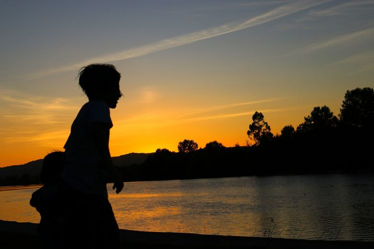 EyeEm Selects Sunset Silhouette One Person Nature Sky Reflection Tranquility Water Outdoors Lake Beauty In Nature Sunrise_sunsets_aroundworld Silhouettes And Shadows Kid