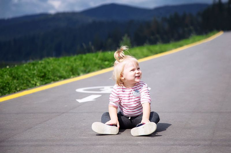 Full length of girl looking away while sitting on road