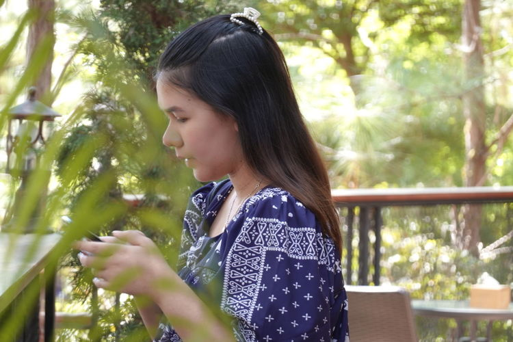 Side view of woman looking at trees