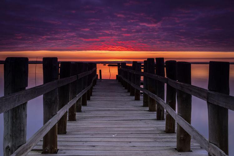 View of pier on sea against orange sky