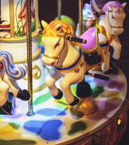 Close-up of carousel horses at night