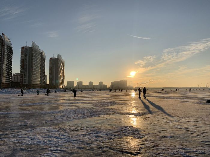 People on beach by buildings against sky during sunset