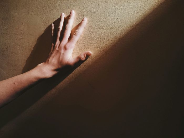 Sunlight falling on cropped hand touching wall