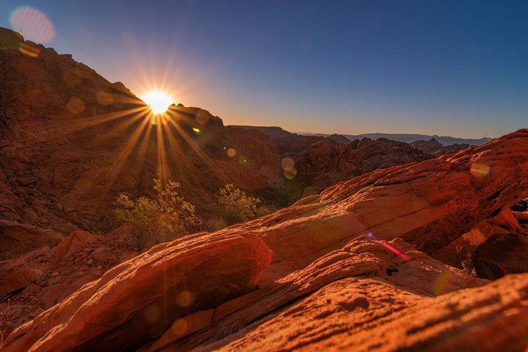 A sunrise in Valley of Fire state park is certainly one to remember. It also gives right to the name of the park in Nevada, USA. Sky Scenics - Nature Mountain Beauty In Nature Sunlight Landscape Tranquility Tranquil Scene Environment Non-urban Scene Sunbeam Nature Sun Lens Flare No People Mountain Range Idyllic Physical Geography Outdoors Climate Land Remote Arid Climate Valley Of Fire State Park USA Nevada Sunrise Red Rocks  Red Scenery Clear Sky