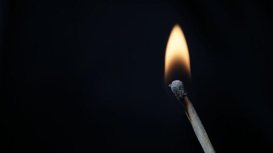 Close-Up Of Illuminated Matchstick Against Black Background