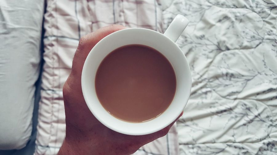 Cropped hand holding coffee cup in bedroom at home