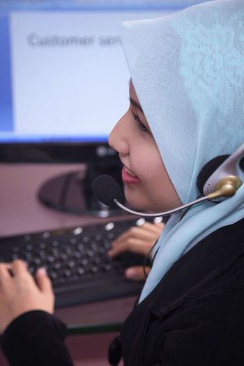 Female customer service representative using computer in office