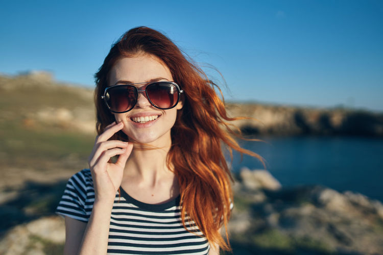 Portrait of smiling young woman using smart phone against sky