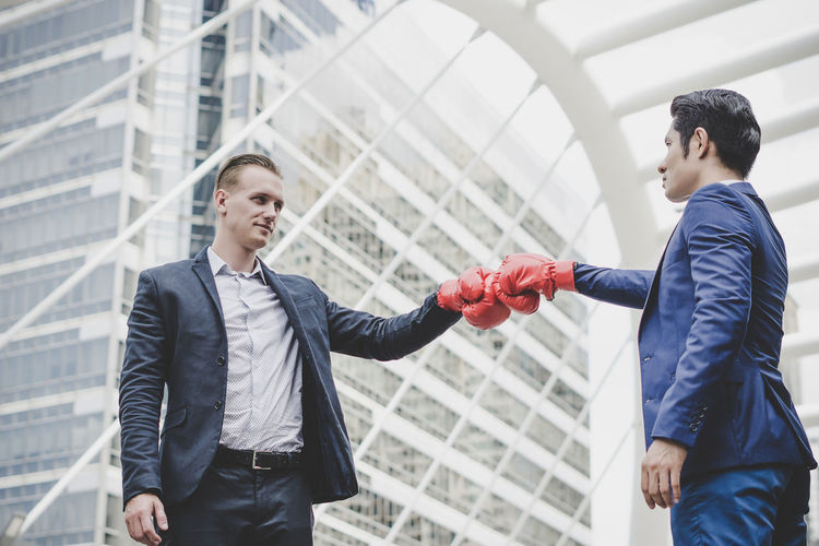 Businessman giving fist bump while standing against metallic structure