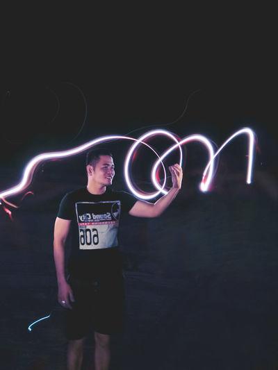 Full length of man standing in illuminated light
