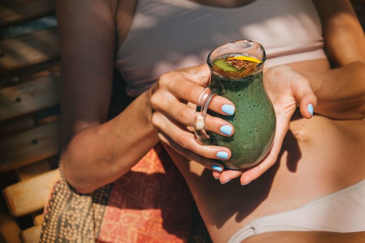 Midsection of woman holding drink in container