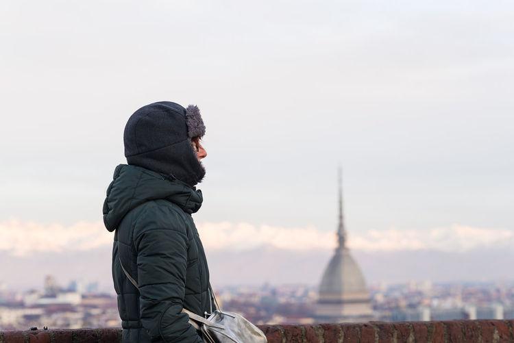 Woman wearing winter coat with mole antonelliana in background