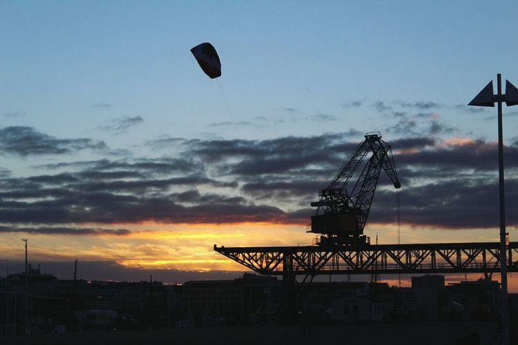 Parachute In The Sky Crane - Construction Machinery Crane Silhouette Sky Water Sunset Like Fire Clouds And Sky Clouds And Sunset  Warm Colors Warm Atmosphere Great Outdoors Best Shots EyeEm