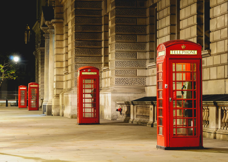 Red telephone booth on sidewalk at night