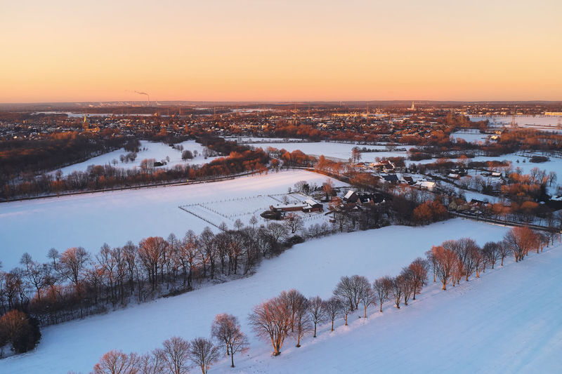 Snow covered agricultural landscape and small towns in industrial area during sunset in the winter