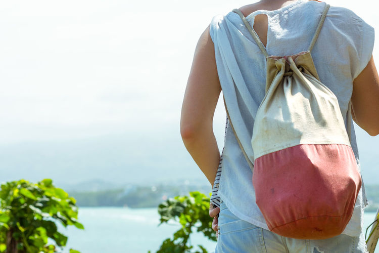Midsection Of Woman Carrying Backpack Walking Against Sky On Sunny Day