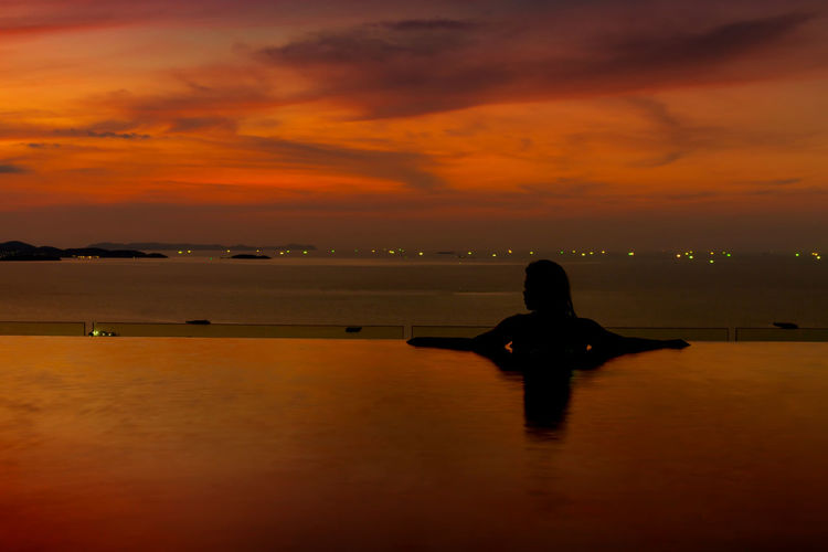Silhouette woman swimming in infinity pool by sea against sky during sunset