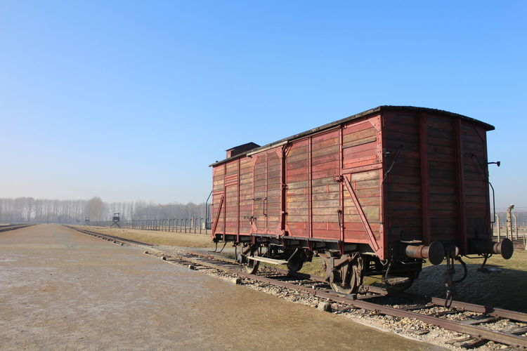 Old abandoned freight train car on track against blue sky