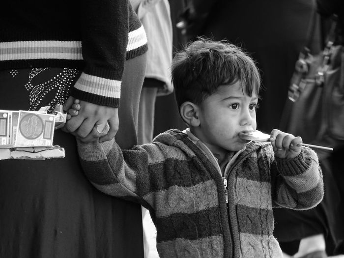 Boy with mother holding lollipop