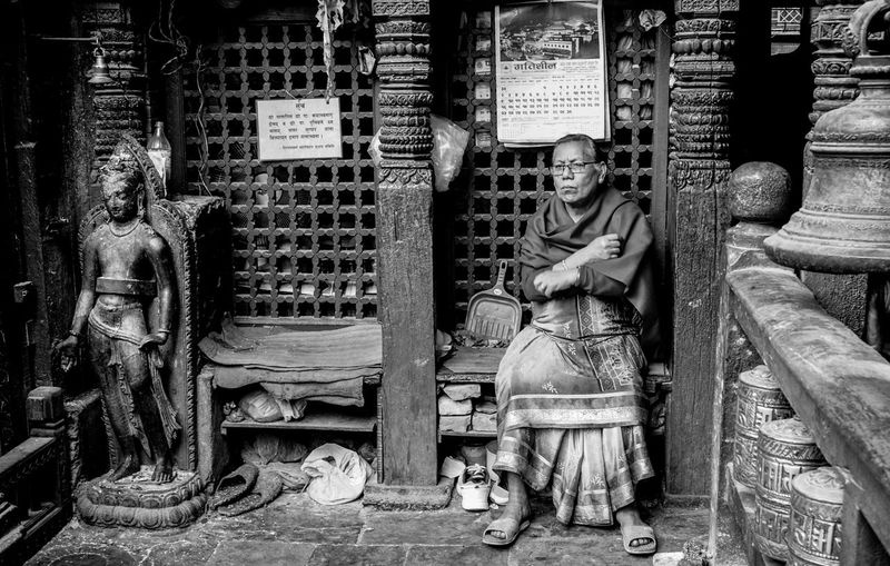 Senior Woman Sitting In Old Buddhist Temple