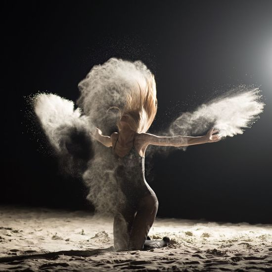Mid adult woman dancing on sand at night