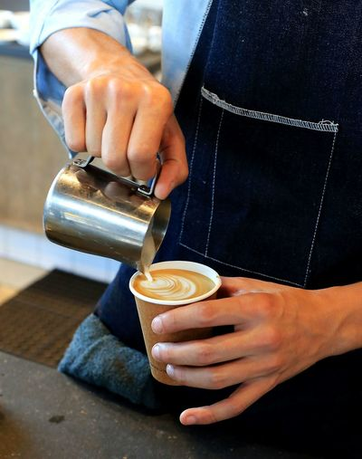 Midsection of barista pouring coffee in cafe
