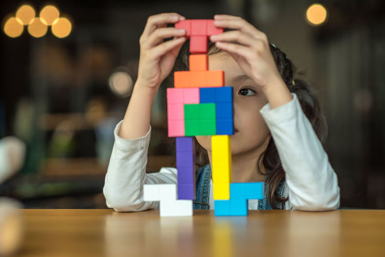 Close-up of girl playing with toy blocks on table