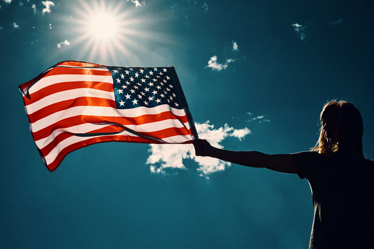 American flag outdoors. woman silhouette holds usa national flag against blue cloudy sky.