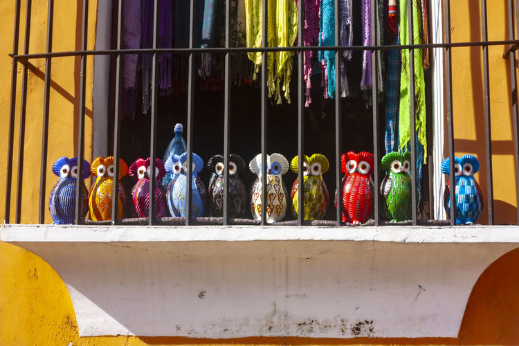 Colored ceramic owls behind a window lattice in Antigua Guatemala Jail Arrangement Art And Craft Ceramic Choice Close-up Creativity Day For Sale Human Representation In A Row Large Group Of Objects Male Likeness Market Multi Colored No People Owl Owls Representation Retail  Retail Display Sale Side By Side Still Life Variation The Street Photographer - 2018 EyeEm Awards EyeEmNewHere The Traveler - 2018 EyeEm Awards The Creative - 2018 EyeEm Awards Summer In The City Autumn Mood Streetwise Photography
