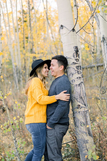 Young couple standing by tree trunk during autumn