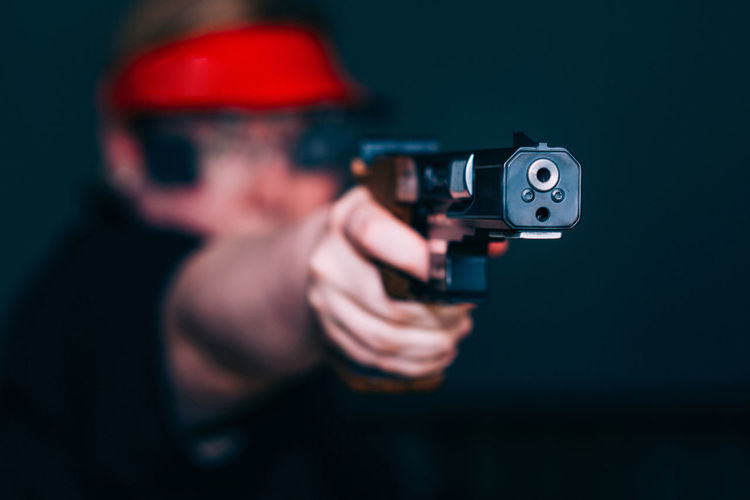 Close-up of woman aiming gun against black background