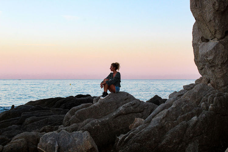 Woman sitting on rock by sea against sky during sunset