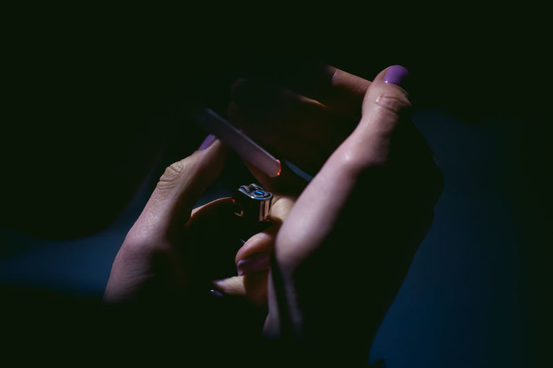 Cropped hands of woman holding cigarette lighter in darkroom